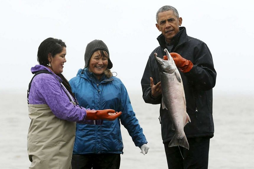 US President Barack Obama (right) holds a natural river salmon as he meets traditional fishermen in Alaska in September 2015.