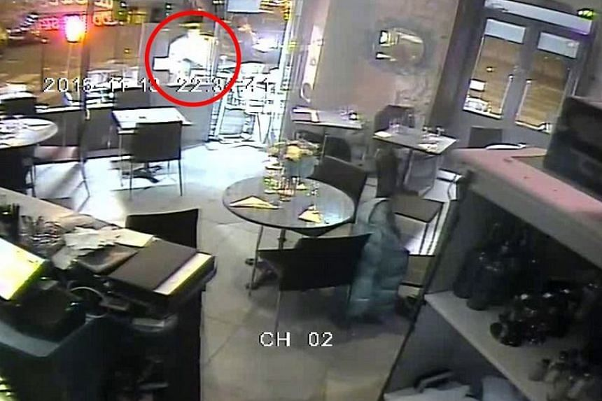 The gunman (circled in red) near the pizzeria entrance where two women were hiding under a table.