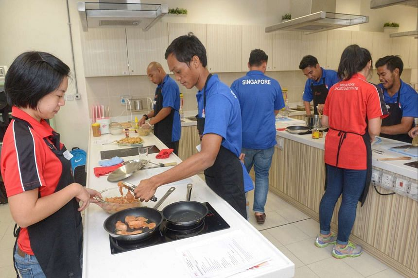 (From left) Singapore Sports institute dietician Cheryl Teo, 27, helping Mr Taufiq Tilo, 26, pan fry a chicken breast.