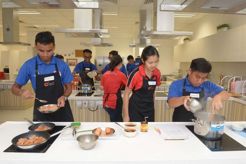 (From left) Mr Muhammad Mubarak, 23, cooking chicken breast with the help of Singapore Sports Institute dietician Ang Sin Hwee, 26, while Mr Jeremiah Tan, 20, makes fried rice.