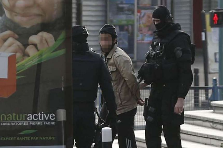 A man being led away after his arrest by policemen in the northern Paris suburb of Saint-Denis yesterday. The raid on an apartment by the French police left two people dead, including a young woman who detonated an explosive vest. Seven people were a