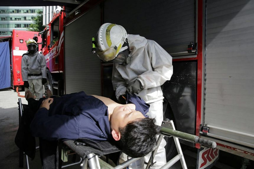 SCDF staff helping a chemical attack victim in yesterday's exercise. Now in its seventh year, the simulation exercise was led by the Singapore Police Force and Singapore Civil Defence Force, and involved a total of 242 officers and community particip
