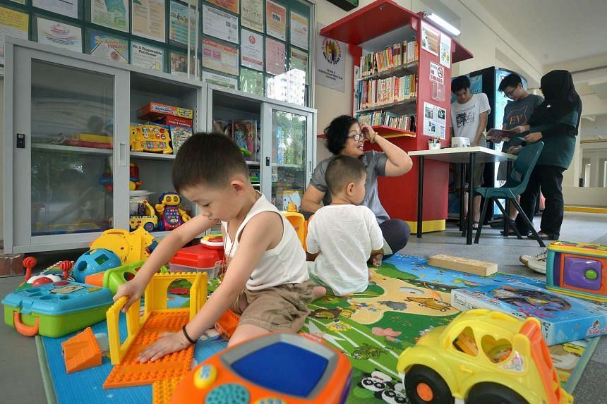 Lee Siang Yu, four, (left) and his brother, Siang Hao, two, with their grandmother, Madam Ho Koon Foong, 61, in the play area of the toy library, while Lim Wee Yang, 16 (standing, in white) and Lai Zi Yang, 16, get help from mobile library assistant Nora