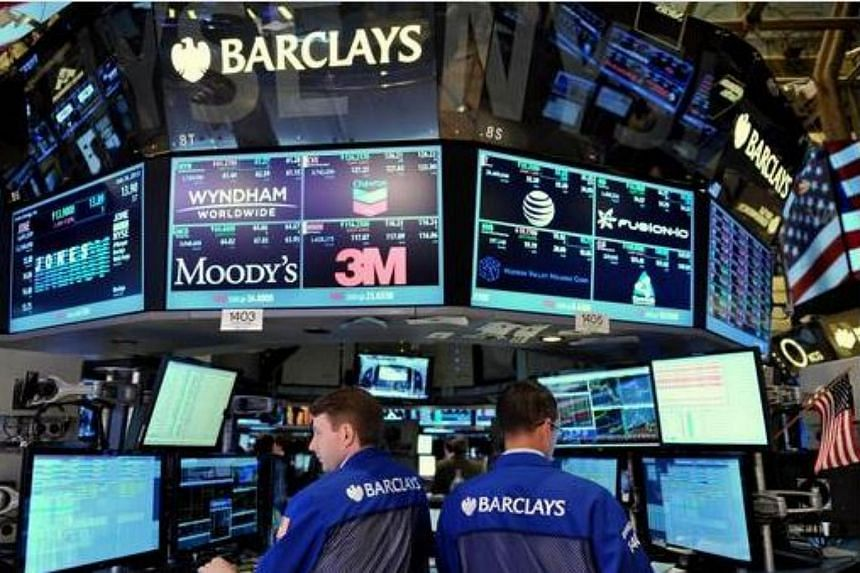 In this July 24, 2013, file photo, specialists work at the Barclays post on the floor of the New York Stock Exchange just after the closing bell in New York.