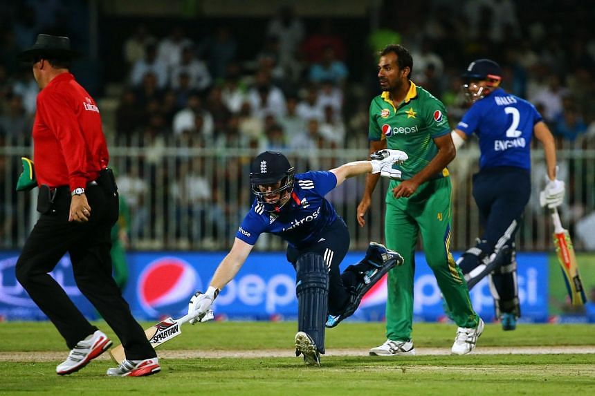 England's Eoin Morgan (centre, front) reaches to safety as he runs between wickets with his teammate Alex Hales (back) on during the third One Day International match between Pakistan and England on Nov 17, 2015.
