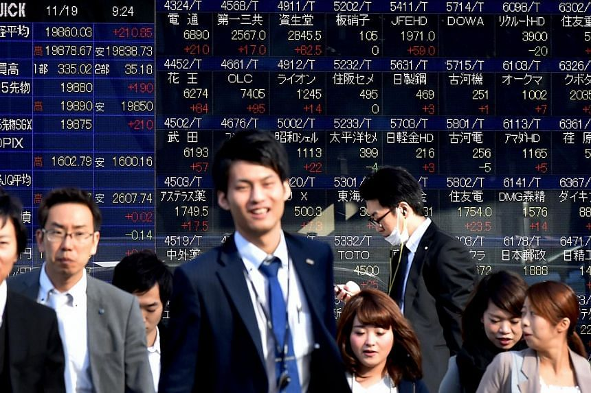 Pedestrians walk past a share prices board of the Tokyo Stock Exchange in Tokyo.