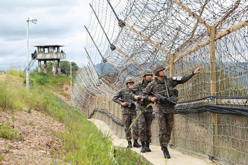 South Korean soldiers patrolling the barbed-wire fence of the Demilitarized Zone (DMZ) separating North and South Korea, in Hwacheon on Aug 26, 2015.