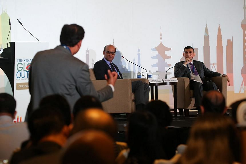 DPM Tharman Shanmugaratnam (centre) and ST editor Warren Fernandez (right) listening to a question from a member of the audience.