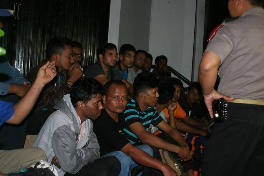 An Indonesian policeman (right) standing next to a group of migrants at an immigration office in Sukabumi.