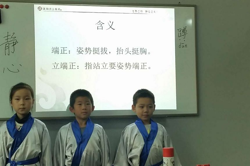 Pupils in class at Hanxiang calligraphy school being taught about posture according to classical Confucian text Dizigui.