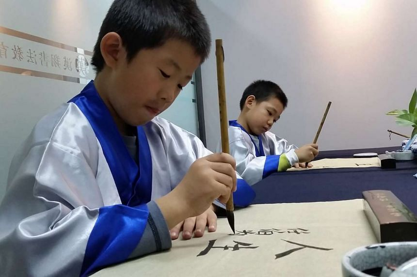 Ren Bowei, 7 (left) and Ji Zhengpeng, 8, practising calligraphy in Hanxiang calligraphy school. Hanxiang, like many other guoxue centres, infuses its classes with Confucian teaching.