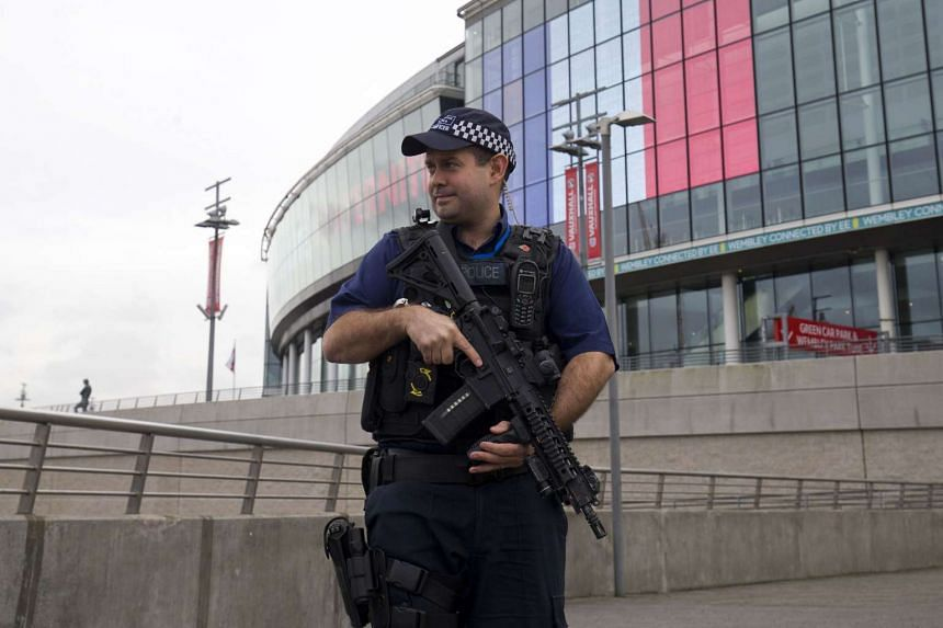 An armed British police officer stands guard at Wembley Stadium in west London, on Nov 17, 2015.