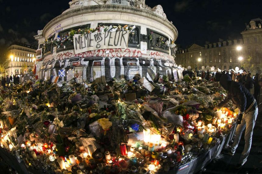 People place candles and flowers at the base of the Monument a la Republique in Paris to pay tribute to the victims of the attacks on Nov 13.