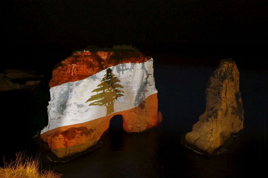 The Pigeon rock is illuminated with the Lebanese national flag in tribute to victims of Thursday's attacks in Beirut's southern suburbs.