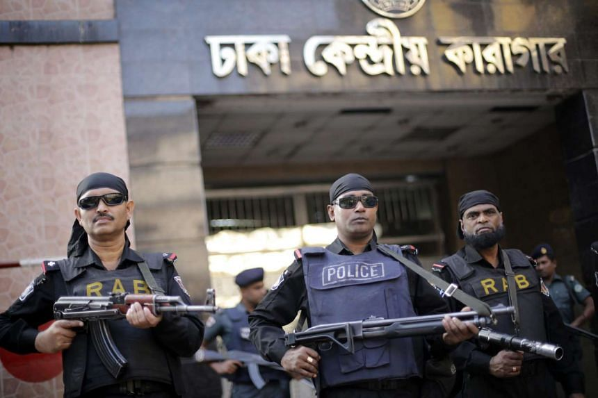 Security members stand guard in front of Dhaka Central Jail as family members meet with the two war criminals.