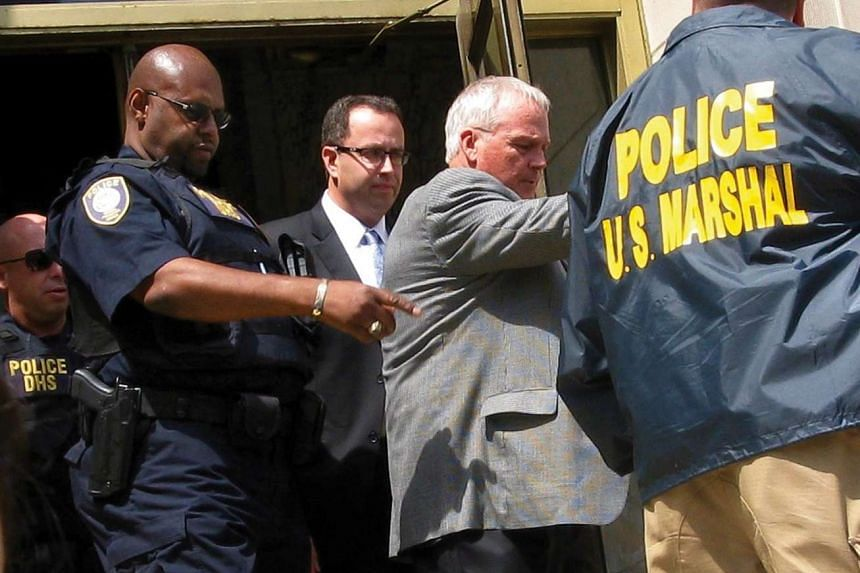 Former Subway sandwich chain pitchman Jared Fogle (centre) is led from federal court in Indianapolis, Indiana, in this file photo taken on Aug 19, 2015.
