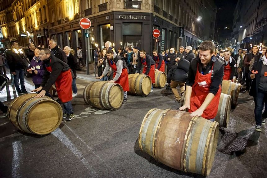 Men roll barrels of Beaujolais for the official launch of the 2015 vintage in Lyon, France.