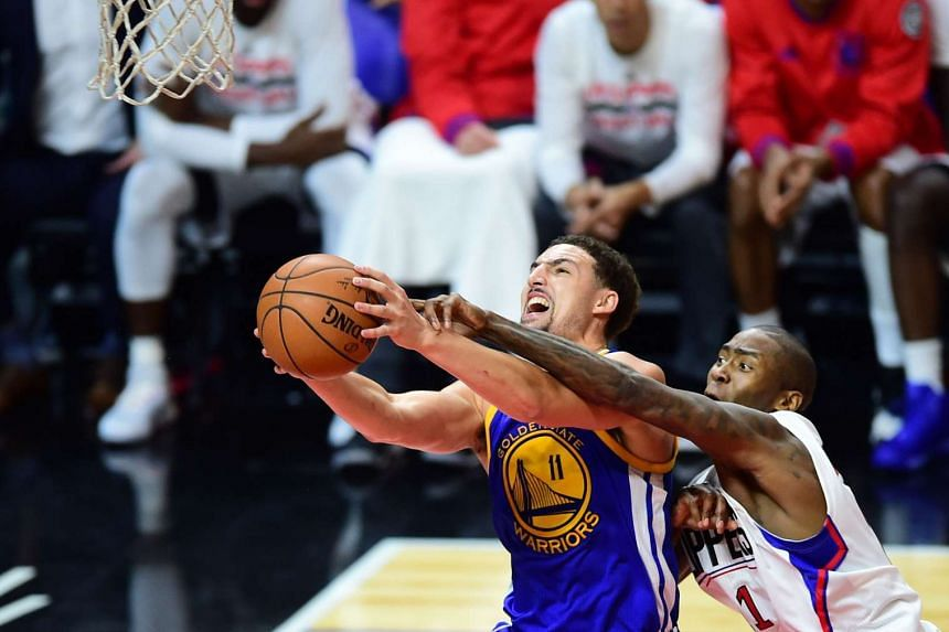 Klay Thompson of the Golden State Warriors goes to the basket under pressure from Jamaal Crawford of the Los Angeles Clippers.
