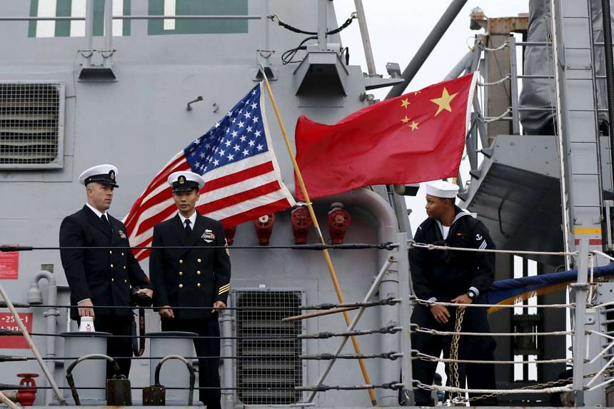 US navy sailors standing in front of American and Chinese flags at a military port in Shanghai on Nov 16.