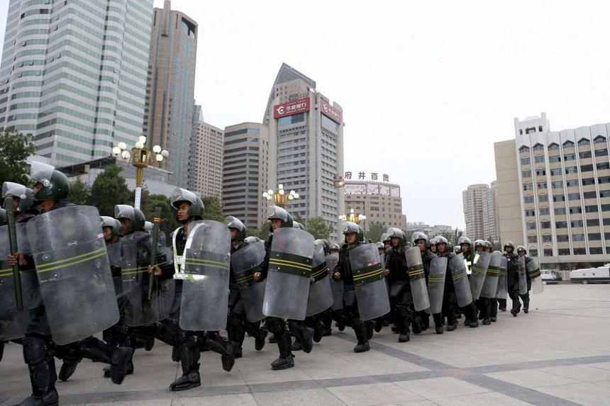 Armed paramilitary policemen run in formation in Xinjiang, China.
