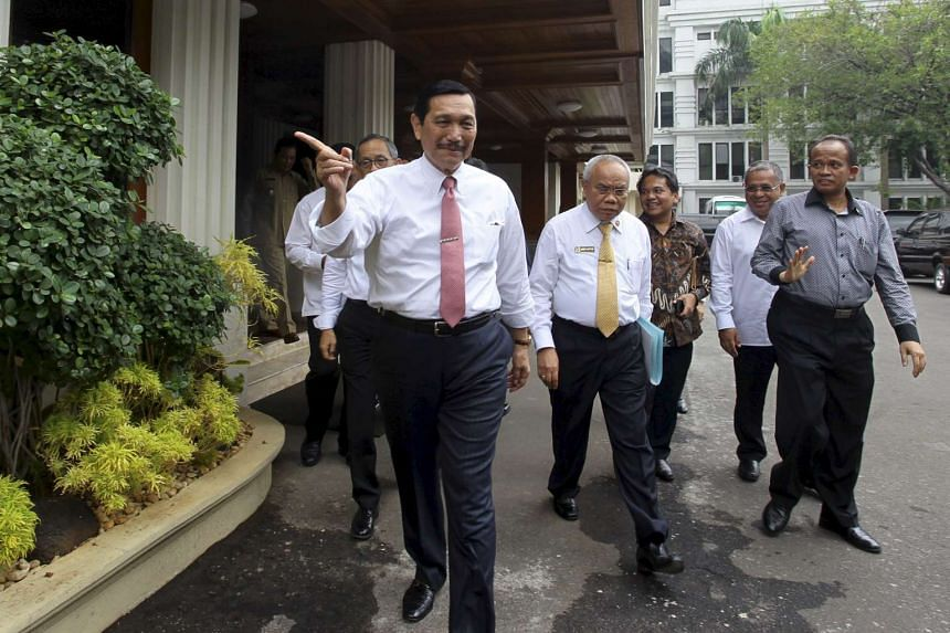 Mr Luhut Pandjaitan (centre) walking with officials to a news conference in Jakarta on Nov 19.