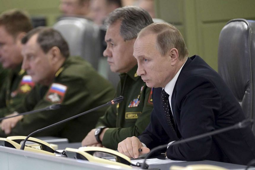 Russian President Vladimir Putin with Defence Minister Sergei Shoigu attend a meeting on Russian air force's activity in Syria.