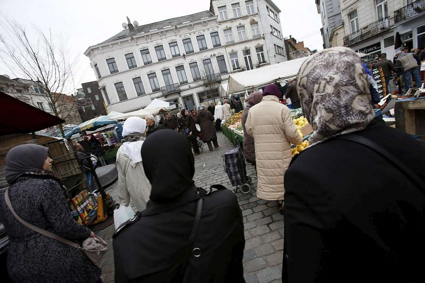 People shop at a market in the neighbourhood of Molenbeek, where several arrests took place.