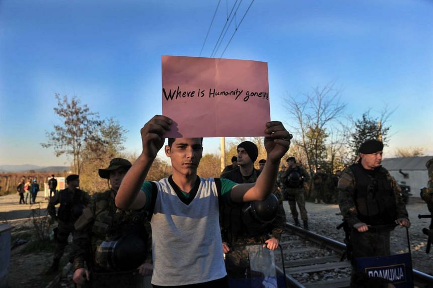 """A man holds a sign reading """"Where is Humanity gone!!!!"""" as migrants and refugees cross the Greece-Macedonia border."""