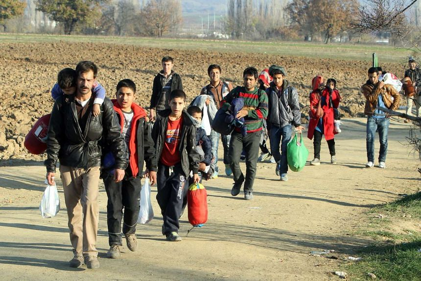Migrants from Syria, Iraq and Afghanistan cross the border between Serbia and Macedonia on Nov 19, 2015.