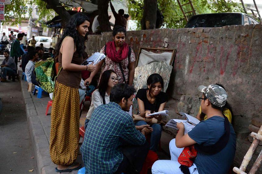 Student activists Shambhawi Vikram (left) and Shriya Subhashini (centre) speaking to fellow students as they distribute leaflets outside Delhi University's North Campus on Sept 30.