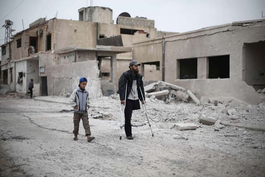 A Syrian man walking with his son amid damaged buildings in the Marj al-Sultan neighbourhood east of the capital Damascus on Oct 25, 2015.