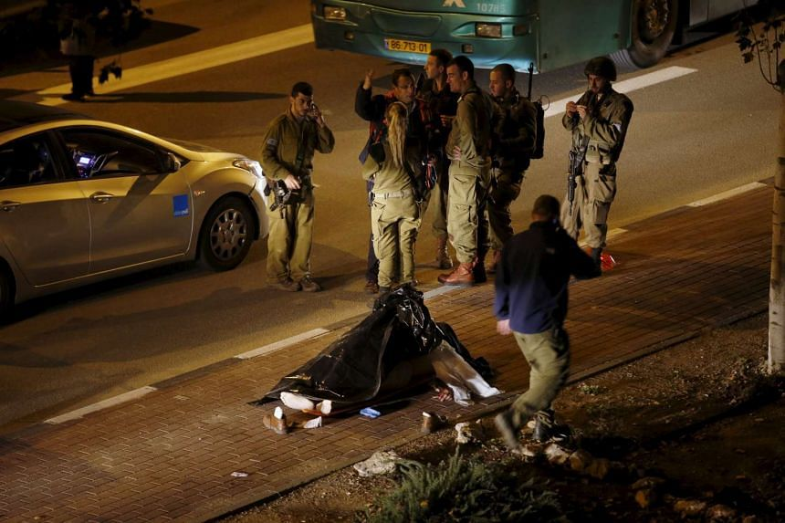Israeli soldiers stand next to a body at the scene of a Palestinian attack near a West Bank settlement.