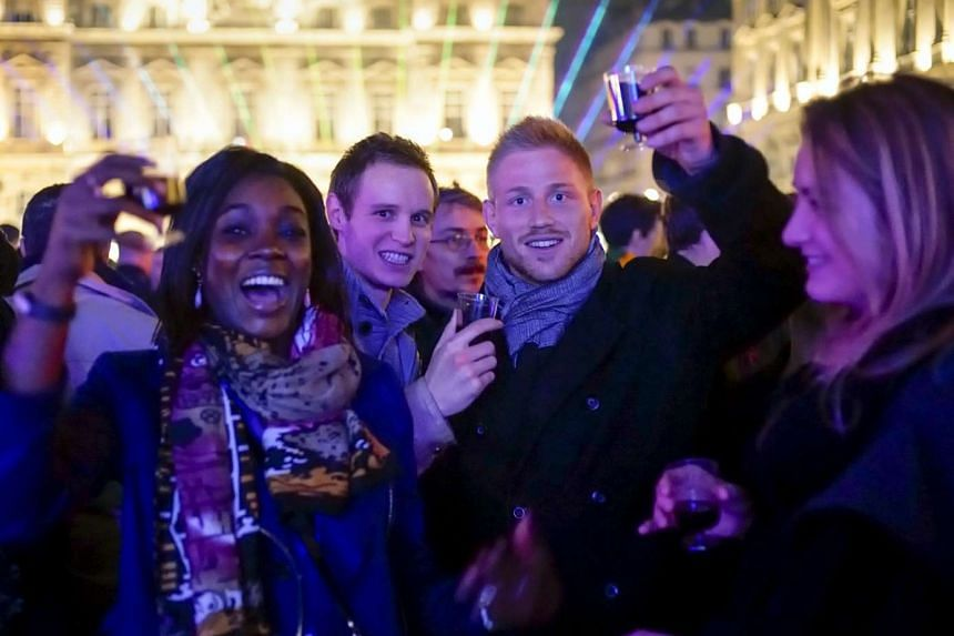 People drink wine during the Beaujolais launch in the center of Lyon, France.