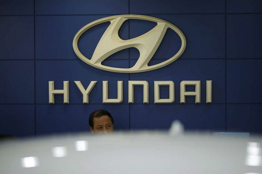An employee sits in front of the logo of Hyundai Motor Co. at its dealership in Seoul, South Korea, on Oct 22, 2015.
