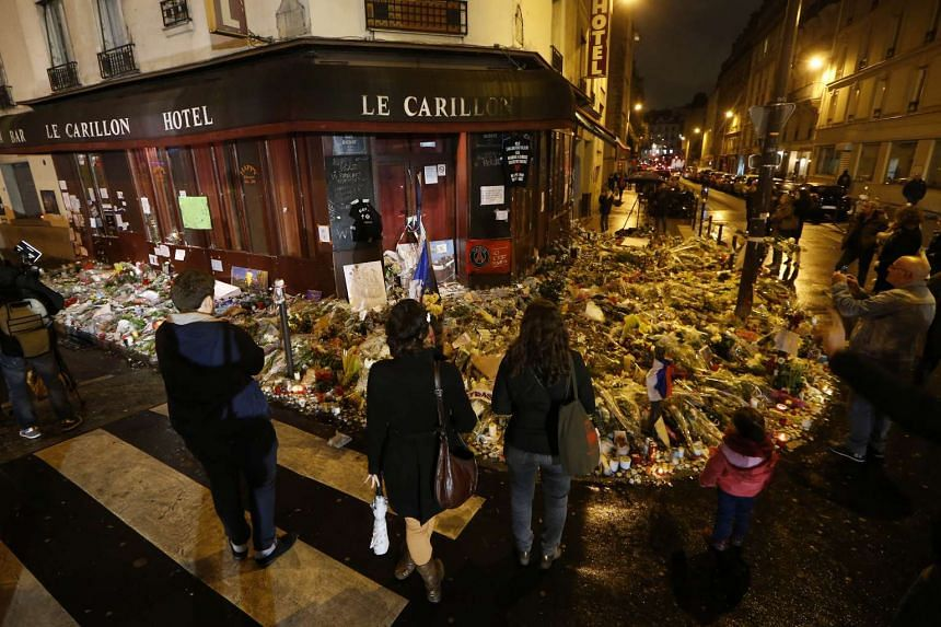 People gather at a memorial in front of the Carillon cafe on rue Bichat and rue Alibert in Paris, one of the locations targetted during the attacks.