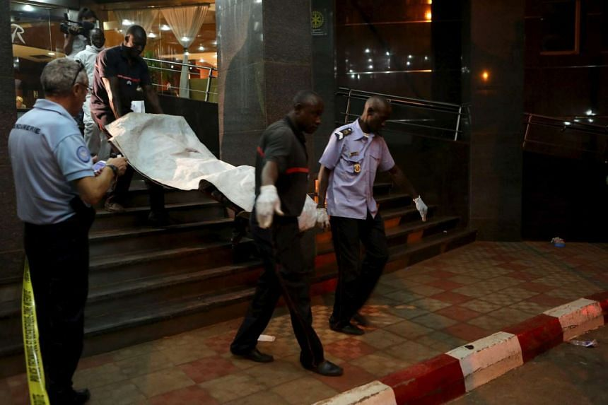 Malian officials carry a body out from the Radisson hotel in Bamako, Mali.