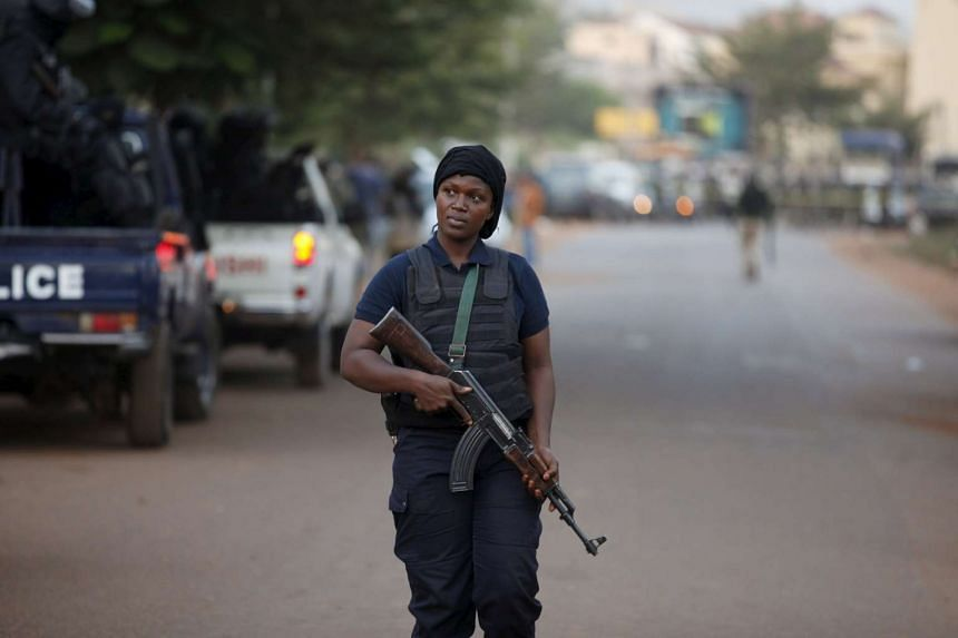 A Malian police officer walking in front of the hotel that was attacked in Bamako.