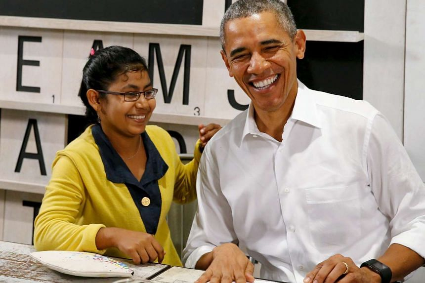 US President Barack Obama (right) smiles with a 16-year old refugee, a victim of human trafficking who will soon be resettled in the US on Nov 21, 2015.