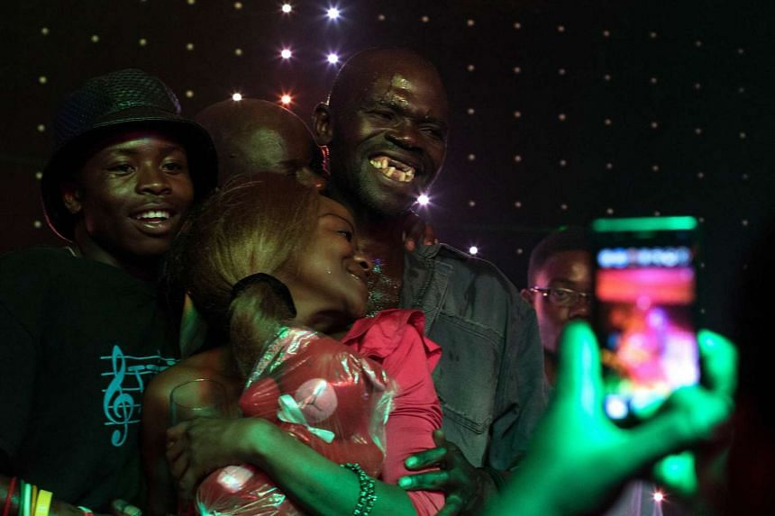 Mr Sere celebrating his victory with members of the audience.