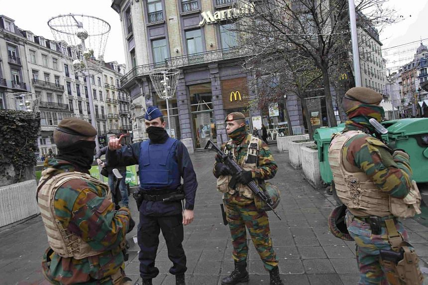Belgian soldiers and a police officer patrol in central Brussels, Nov 21.