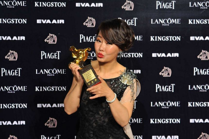 Taiwan actress Lu Xuefeng poses with her trophy after winning the Supporting Actress award during the 52nd Golden Horse Film Awards.