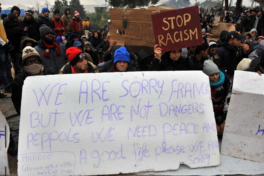 Migrants and refugees hold a placard refering to Paris' attacks during a protest as they wait to cross the border between Greece and Macedonia near the vilage of Idomeni on Nov 21, 2015.