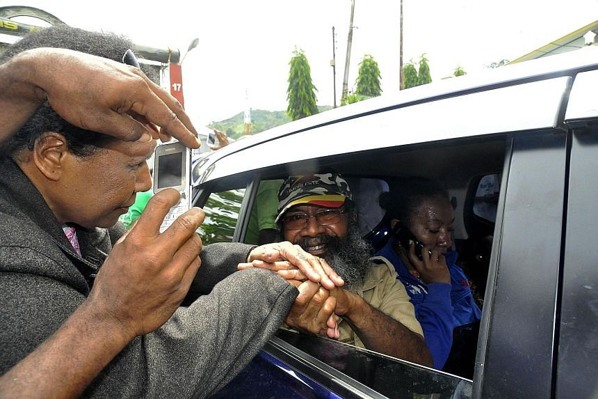 Papuan pro- independence activist Filep Karma (in vehicle) greeting his supporters after being released from prison in Abepura, Papua province, on Thursday. The high-profile Papuan separatist leader was released from prison after more than a decade b