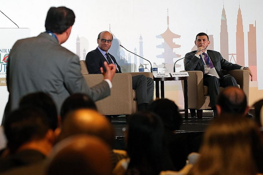 One of the about 400 participants, including ST readers, at The Straits Times Global Outlook Forum engaging Deputy Prime Minister Tharman Shanmugaratnam during a Q&A session moderated by Straits Times editor Warren Fernandez yesterday.