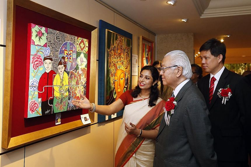 """Artist Shivali Mathur showing President Tony Tan Keng Yam the painting Integration, which she says is a representation of the way that culture """"comes together as one"""" in Singapore. With them is Minister in the Prime Minister's Office Chan Chun Sing."""