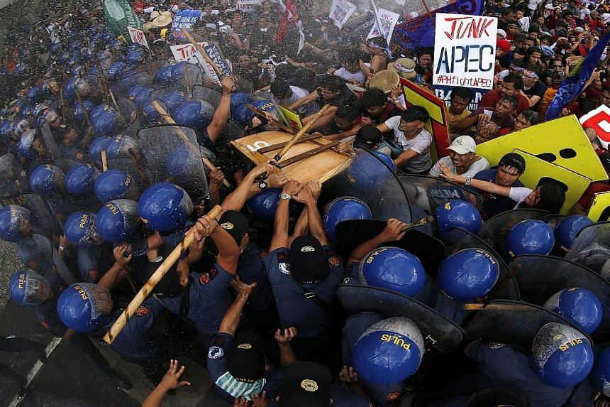 "Activists clashing with police in Manila on Thursday. Apec has been slammed as nothing more than a peripatetic photo-op, with ""family photos"" of Apec leaders dressed in the host country's national dress."