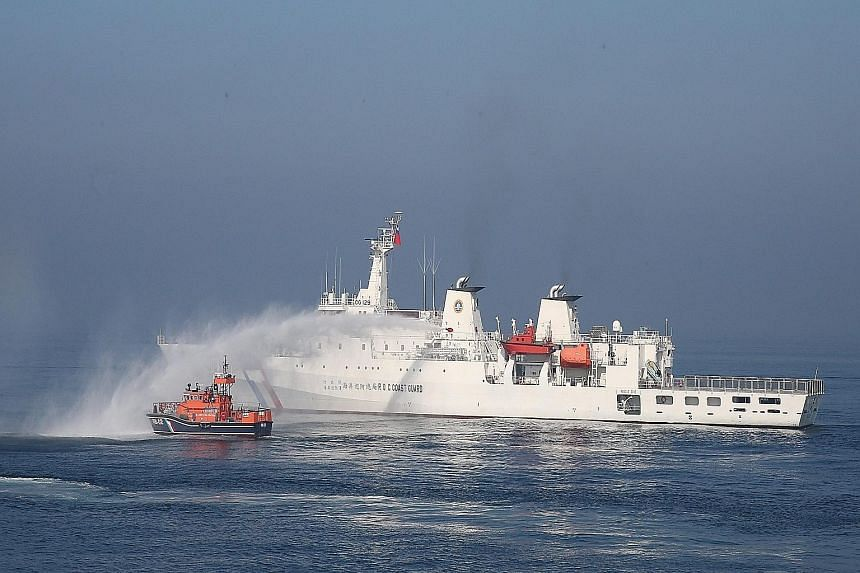 """A Taiwanese patrol boat using a water cannon to repel a """"foreign fishing boat"""" during a drill held off the coast of Kaohsiung, in southern Taiwan, on Tuesday. On Thursday, Taiwan's Foreign Ministry said that Taiwan and the Philippines have signed a f"""