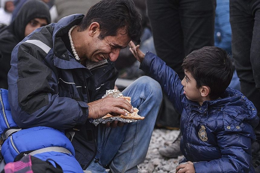 A boy consoling his father at the border between Greece and Macedonia. Macedonia started granting passage only to refugees from war-affected nations like Syria, Iraq and Afghanistan yesterday.