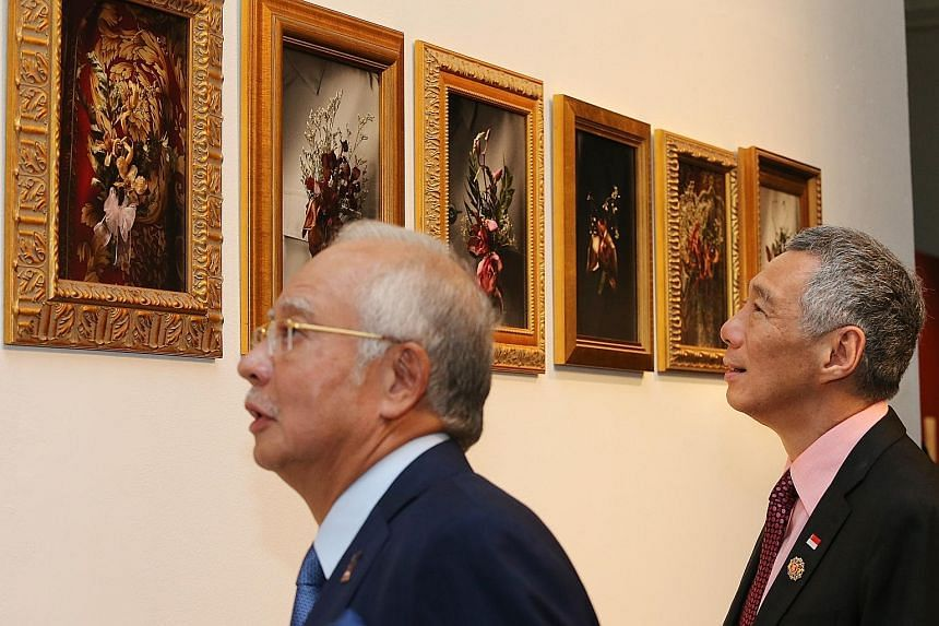 Prime Minister Lee Hsien Loong and Malaysian Prime Minister Najib Razak viewing some exhibits during yesterday's launch of the Titian Budaya arts showcase at the White Box @ Publika space in Kuala Lumpur.