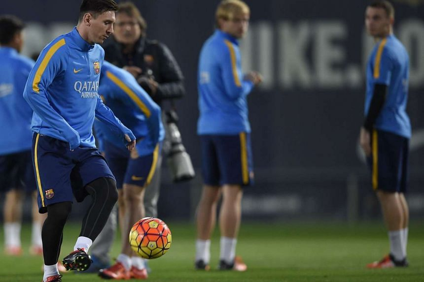Barcelona's Argentinian forward Lionel Messi (left) playing with a ball during a training session at the Sports Center FC Barcelona Joan Gamper on Nov 20, 2015.